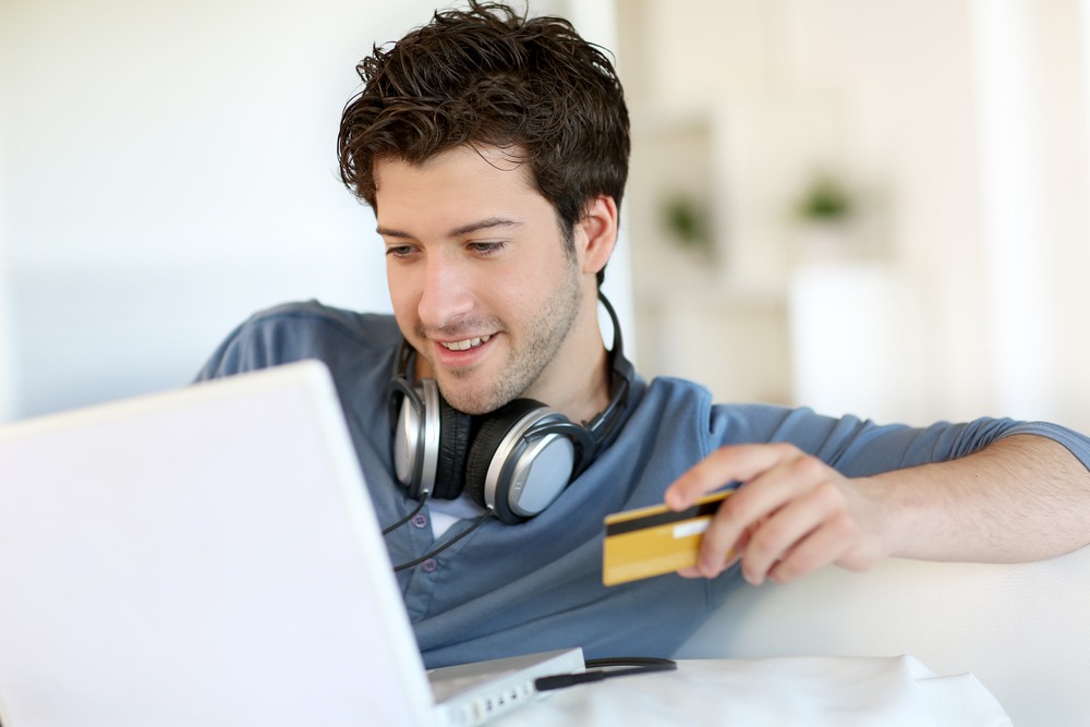 Young man buying music on internet with tablet